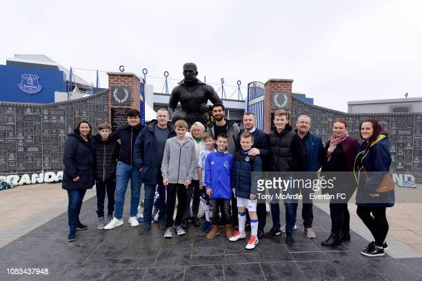 Andre Gomes of Everton poses for a photograph with fans before surprises a young Everton fan with a trip to the club shop at Goodison Park on October...