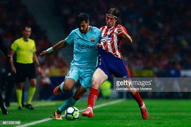 Andre Gomes of FC Barcelona competes for the ball with Filipe Luis of Atletico de Madrid during the La Liga match between Club Atletico Madrid and FC...