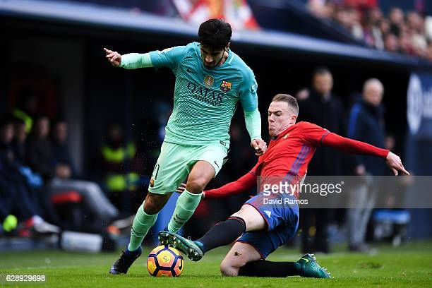 Andre Gomes of FC Barcelona competes for the ball with Javier Flano of CA Osasuna during the La Liga match between CA Osasuna and FC Barcelona at...