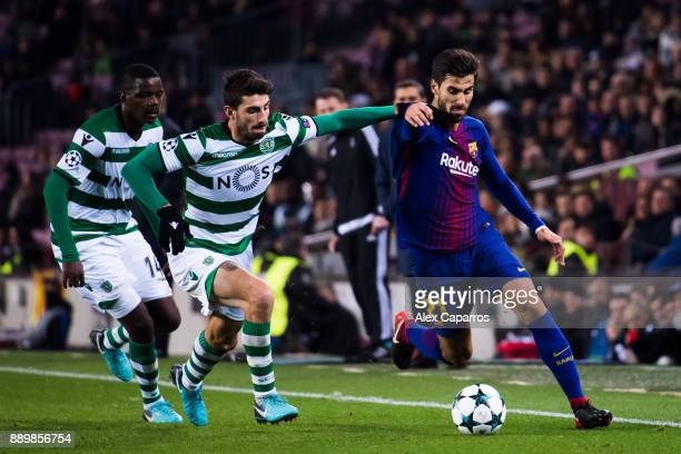 Andre Gomes of FC Barcelona conducts the ball under pressure from Cristiano Piccini and William Carvalho of Sporting CP during the UEFA Champions...