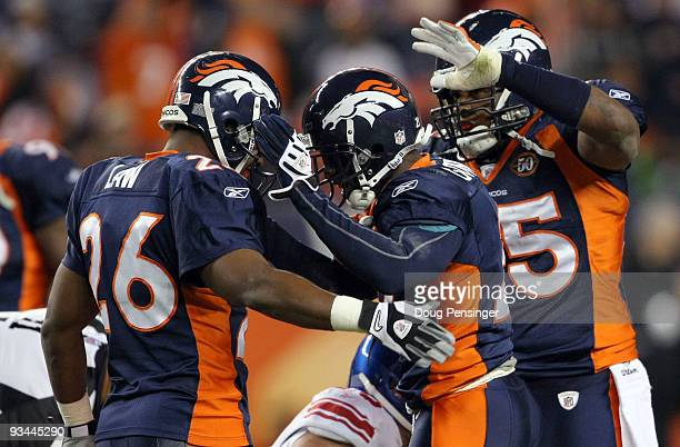 Andre Goodman of the Denver Broncos is congratulated by Ty Law and DJ Williams after his fourth quarter interception of quarterback Eli Manning of...