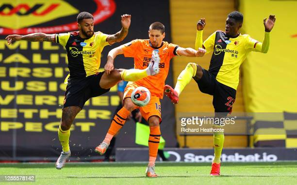 Andre Gray and Ismaila Sarr of Watford battle for possession with Federico Fernandez of Newcastle United during the Premier League match between...