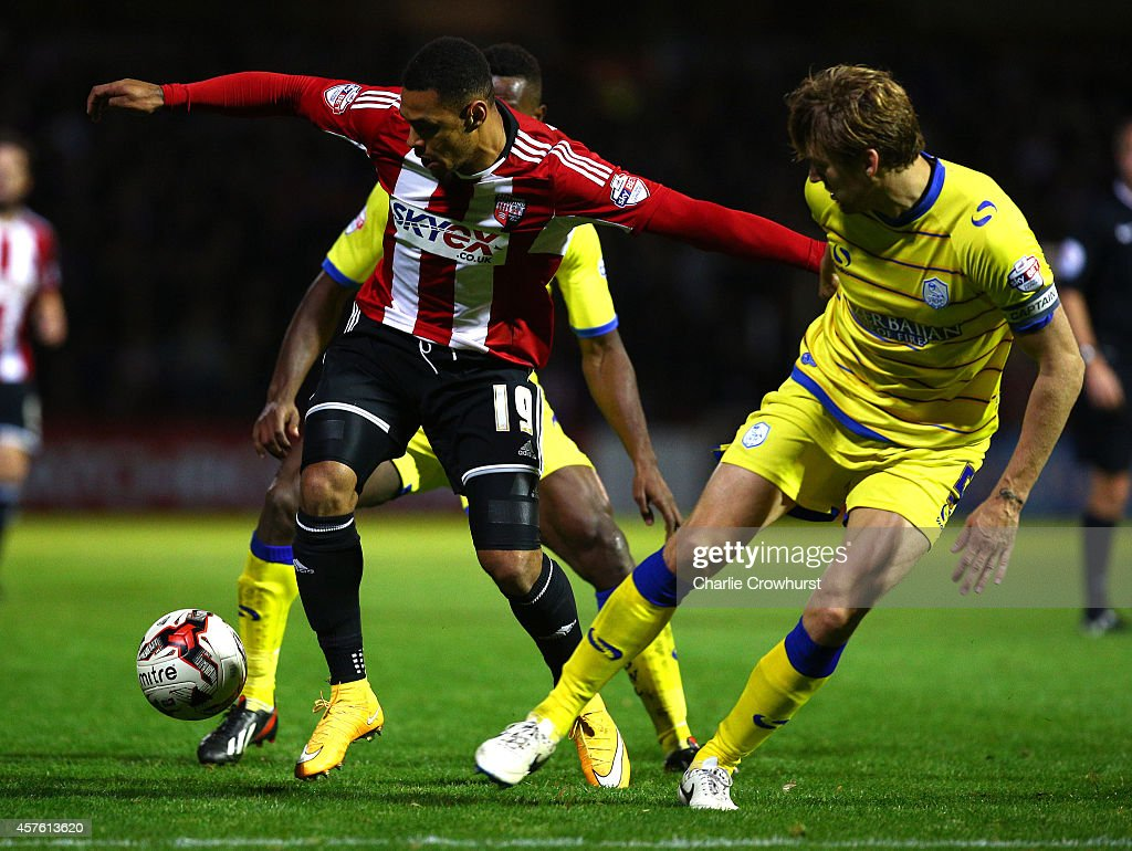 Andre Gray of Brentford holds off Sheffield Wednesdays Tom Lees during the Sky Bet Championship match between Brentford and Sheffield Wednesday at Griffin Park on October 21, 2014 in Brentford, England.