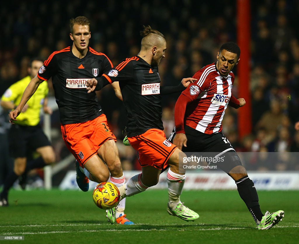 Andre Gray of Brentford looks to get past Fulham's Kostas Stafylidis during the Sky Bet Championship match between Brentford and Fulham at Griffin Park on November 21, 2014 in Brentford, England,