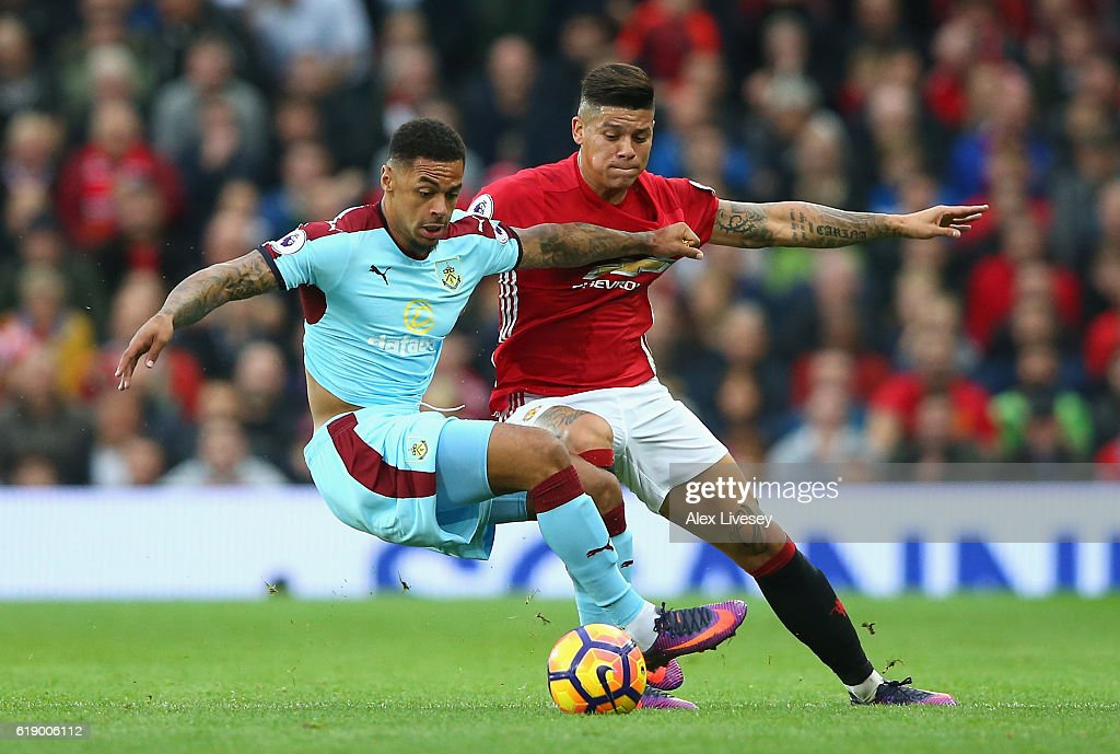 Andre Gray of Burnley (L) and Marcos Rojo of Manchester United (R) battle for possession during the Premier League match between Manchester United and Burnley at Old Trafford on October 29, 2016 in Manchester, England.