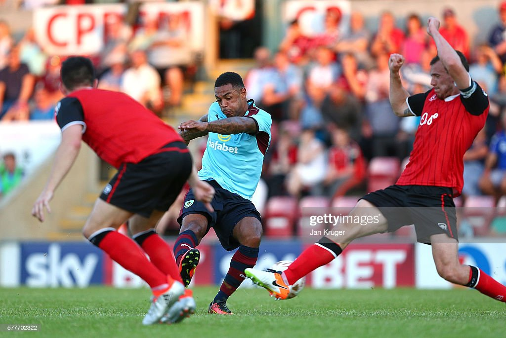 Andre Gray of Burnley shoots at goal under pressure from Dean Winnard of Morecambe during the pre season friendly match between Morecambe and Burnley at Globe Arena on July 19, 2016 in Morecambe, England.