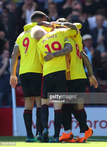 Andre Gray of Watford celebrates scoring his side's second goal with team mates Will Hughes and Troy Deeney during the Premier League match between...