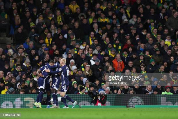 Andre Gray of Watford celebrates with his teammates after scoring his sides second goal during the Premier League match between Norwich City and...