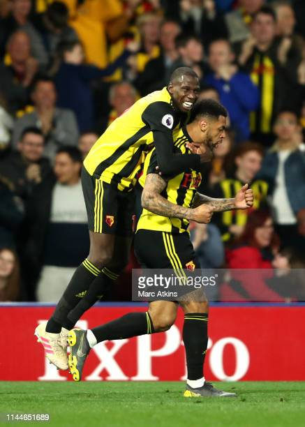 Andre Gray of Watford celebrates with teammate Abdoulaye Doucoure after scoring his team's first goal during the Premier League match between Watford...