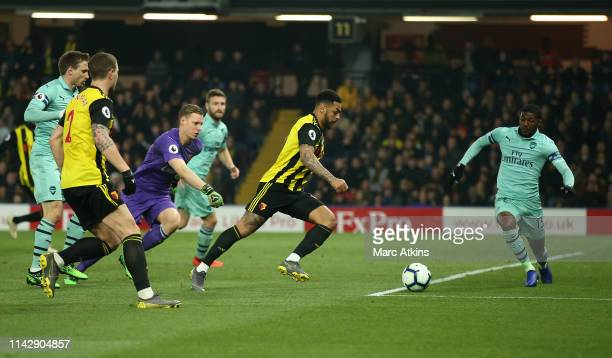 Andre Gray of Watford has his shot at goal blocked by Ainsley MaitlandNiles of Arsenal during the Premier League match between Watford FC and Arsenal...