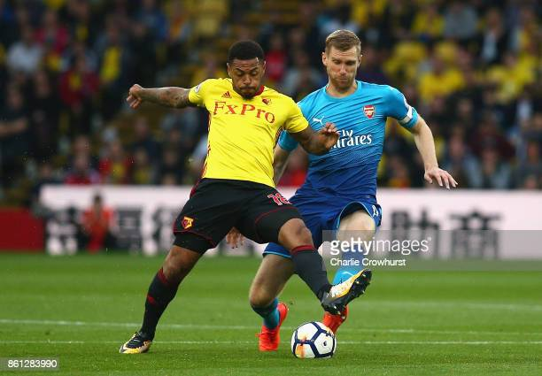 Andre Gray of Watford is closed down by Per Mertesacker of Arsenal during the Premier League match between Watford and Arsenal at Vicarage Road on...
