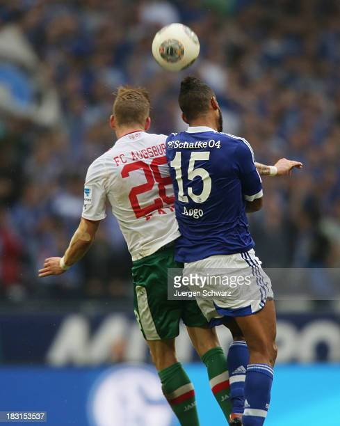 Andre Hahn of Augsburg and Dennis Aogo of Schalke jump for the header during the Bundesliga match between FC Schalke 04 and FC Augsburg at...