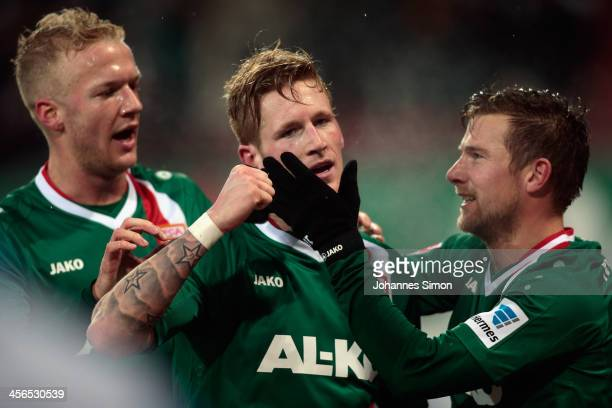 Andre Hahn of Augsburg is congratulated by teammates Kevin Vogt and Daniel Baier after scoring their team's third goal during the Bundesliga match...