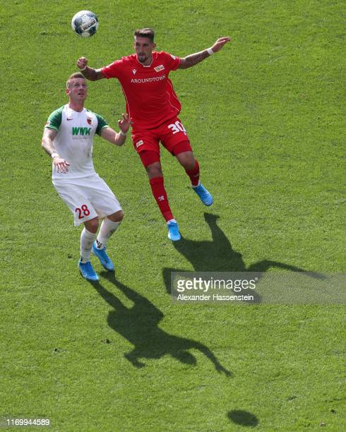 Andre Hahn of Augsburg is tackled by Nico Elvedi of Borussia Monchengladbach during the Bundesliga match between FC Augsburg and 1. FC Union Berlin...
