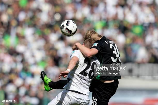 Andre Hahn of Borussia Moenchengladbach and Martin Hinteregger of FC Augsburg battle for the ball during the Bundesliga Match between Borussia...