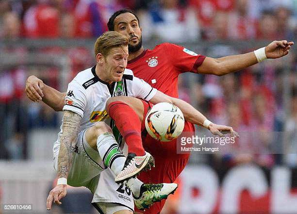 Andre Hahn of Borussia Moenchengladbach and Medhi Benatia of Bayern Muenchen compete for the ball during the Bundesliga match between FC Bayern...
