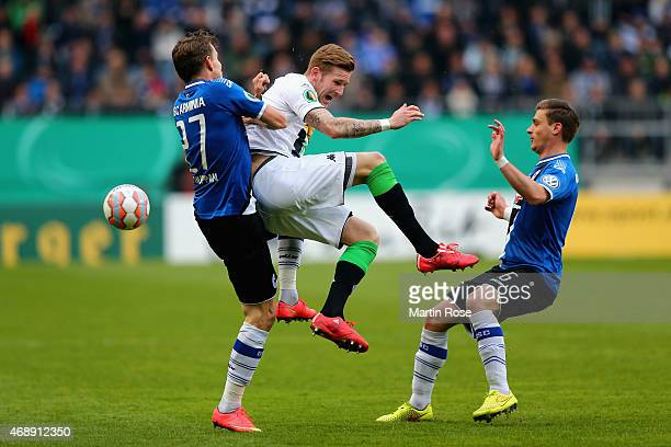 Andre Hahn of Borussia Moenchengladbach is challenged by Sebastian Schuppan and Tom Schuetz of Arminia Bielelfeld during the DFB Cup Quarter Final...