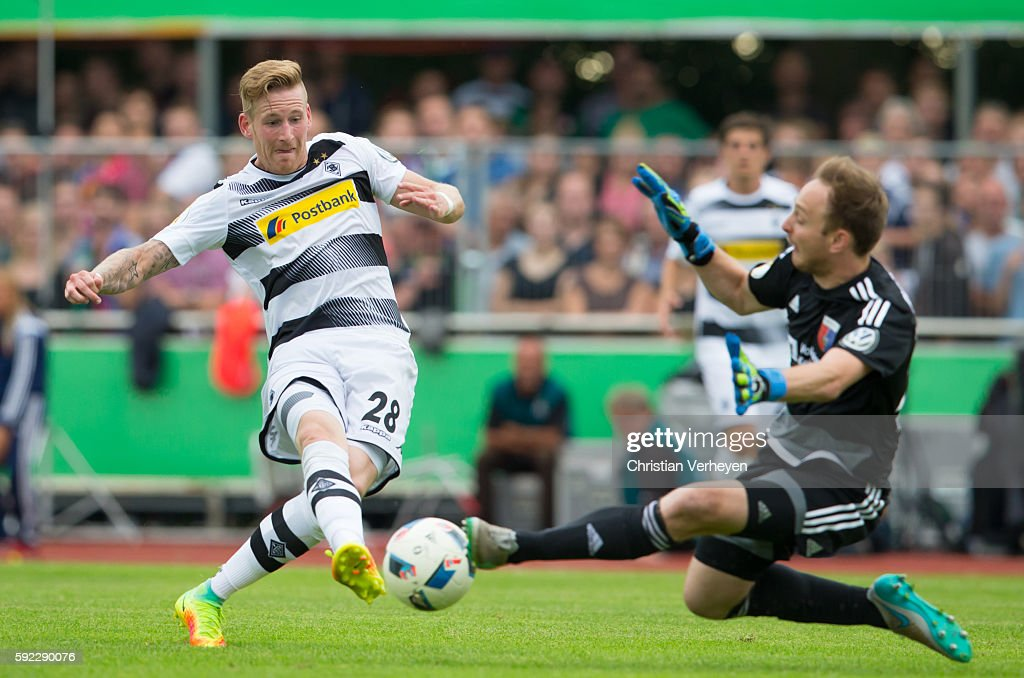 Andre Hahn of Borussia Moenchengladbach try to score against Patrick Siefkes of SV Drochtersen/Assel during the DFB Cup match between SV Drochtersen/Assel and Borussia Moenchengladbach at Kehdinger Stadion on August 20, 2016 in Drochtersen, Germany.