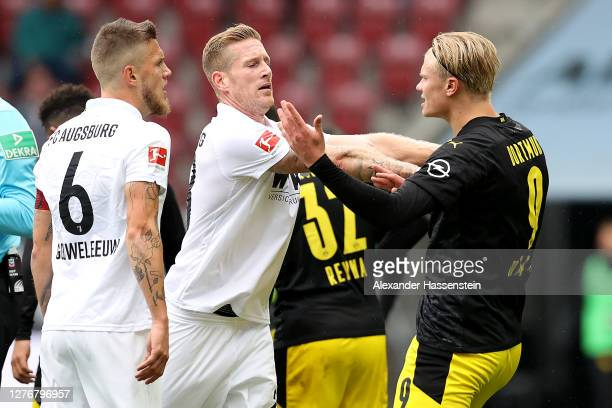 Andre Hahn of FC Augsburg and Erling Haaland of Borussia Dortmund clash during the Bundesliga match between FC Augsburg and Borussia Dortmund at...