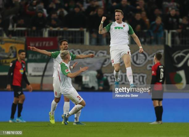 Andre Hahn of FC Augsburg celebrates his first goal with teammates Rani Khedira and Philipp Max during the Bundesliga match between FC Augsburg and...