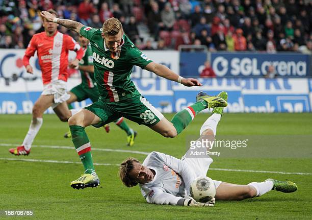 Andre Hahn of FC Augsburg jumps over goalkeeper Christian Wetklo of FSV Mainz during the Bundesliga match between FC Augsburg v 1 and FSV Mainz 05 at...