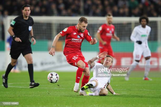 Andre Hahn of FC Augsburg tackles Alexandru Maxim of FSV Mainz during the DFB Cup match between FC Augsburg and 1 FSV Mainz 05 at WWKArena on October...