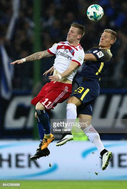 Andre Hahn of Hamburg jumps for a header with Marcel Halstenberg of Leipzig during the Bundesliga match between Hamburger SV and RB Leipzig at...