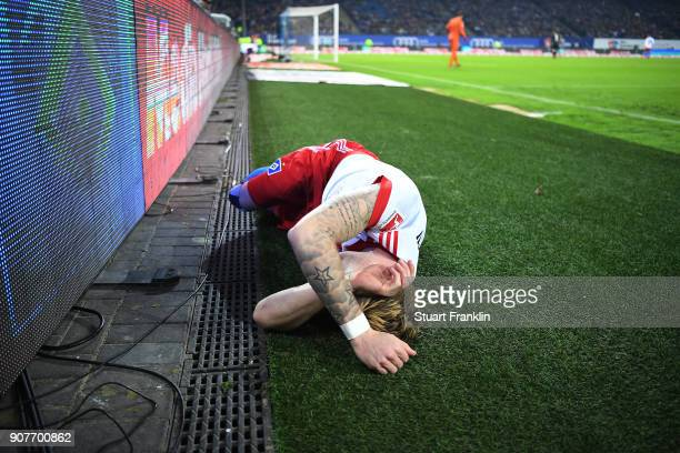 Andre Hahn of Hamburg lies on the pitch in pain after he crashed into the banner during the Bundesliga match between Hamburger SV and 1 FC Koeln at...