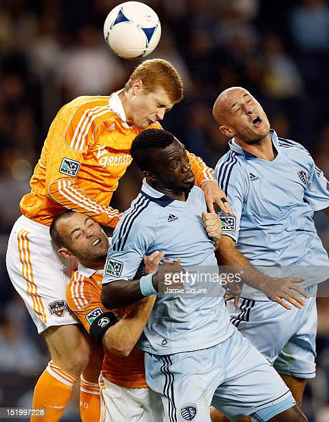 Andre Hainault of the Houston Dynamo battles Brad Davis CJ Sapong and Aurelien Collin of Sporting KC for a header during the MLS game at Livestrong...
