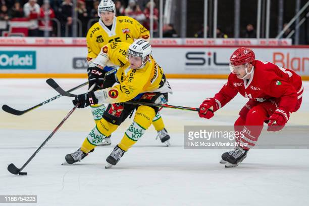 Andre Heim of SC Bern battles for the puck with Joel Vermin of Lausanne HC during the Swiss National League game between Lausanne HC and SC Bern at...