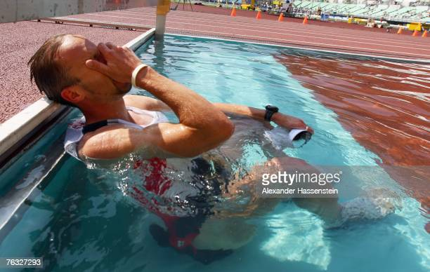 Andre Hohne of Germany reacts to being disqualified near the end of the race by diving into a steeplechase water jump during the Men's 20K Walk final...