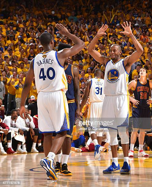 Andre Iguodala and Harrison Barnes of the Golden State Warriors give each other high fives against the Cleveland Cavaliers at the Oracle Arena During...