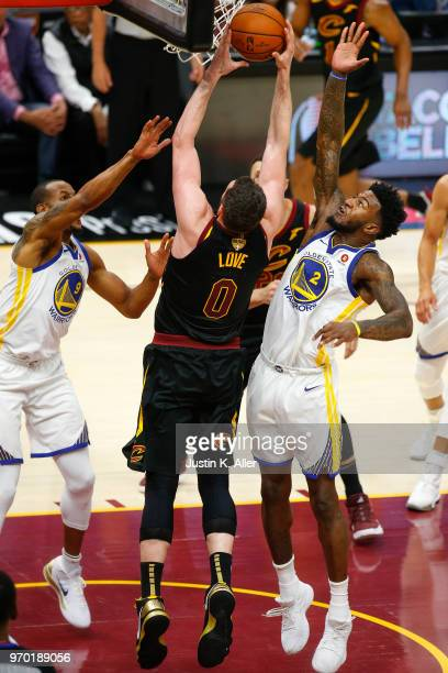 Andre Iguodala and Jordan Bell of the Golden State Warriors fight for a rebound with Kevin Love of the Cleveland Cavaliers during Game Four of the...