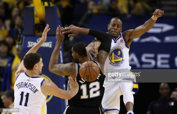Andre Iguodala and Klay Thompson of the Golden State Warriors stop LaMarcus Aldridge of the San Antonio Spurs from scoring during Game Five of Round...
