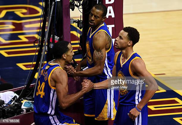 Andre Iguodala and Stephen Curry help Shaun Livingston of the Golden State Warriors to his feet during Game Four of the 2015 NBA Finals against the...