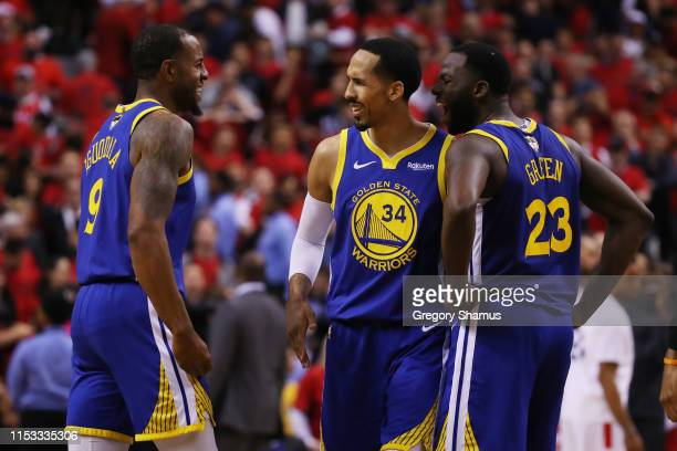 Andre Iguodala is congratulated by his teammates Shaun Livingston and Draymond Green of the Golden State Warriors after scoring a basket against the...