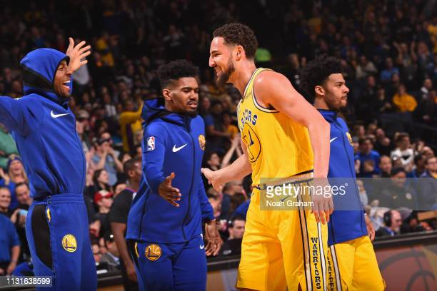 Andre Iguodala Klay Thompson Jacob Evans of the Golden State Warriors exchange hifives during the game against the Phoenix Suns on March 10 2019 at...