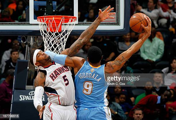 Andre Iguodala of the Denver Nuggets dunks and draws a foul from Josh Smith of the Atlanta Hawks at Philips Arena on December 5 2012 in Atlanta...