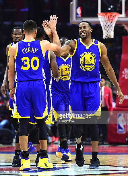 Andre Iguodala of the Golden State Warriors and Stephen Curry celebrate a basket after a timeout against the LA Clippers during the first half at...