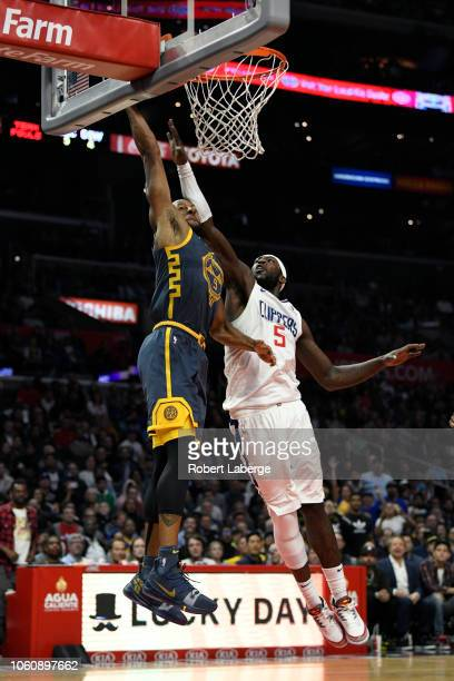 Andre Iguodala of the Golden State Warriors attempts a lay up against Montrezl Harrell of the Los Angeles Clippers on November 12 2018 at STAPLES...