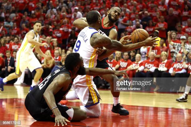 Andre Iguodala of the Golden State Warriors competes for a loose ball in the second half with James Harden and Chris Paul of the Houston Rockets in...