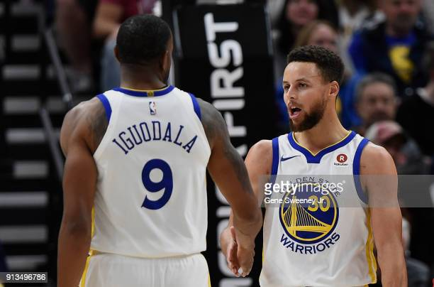 Andre Iguodala of the Golden State Warriors congratulates teammate Stephen Curry during a game against the Utah Jazz at Vivint Smart Home Arena on...