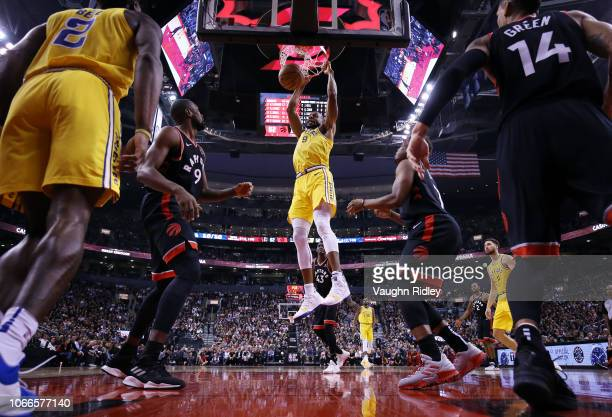 Andre Iguodala of the Golden State Warriors dunks the ball as Serge Ibaka and Kyle Lowry of the Toronto Raptors defend during the first half of an...