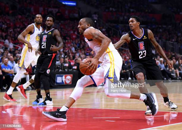 Andre Iguodala of the Golden State Warriors is fouled by Lou Williams of the LA Clippers as he drives to the basket during Game Two of Round One of...