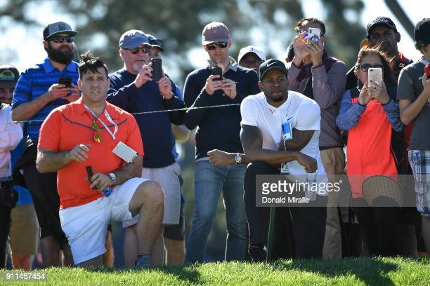 Andre Iguodala of the Golden State Warriors looks on as Tiger Woods plays during the final round of the Farmers Insurance Open at Torrey Pines South...