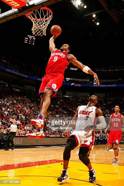 Andre Iguodala of the Philadelphia 76ers dunks against Dwyane Wade of the Miami Heat on November 26 2010 at American Airlines Arena in Miami Florida...