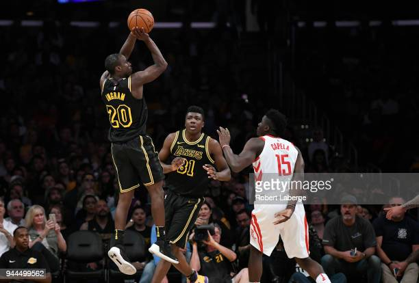 Andre Ingram of the Los Angeles Lakers attempts a jumpshot against Clint Capela of the Houston Rockets as Thomas Bryant of the Lakers looks on on...