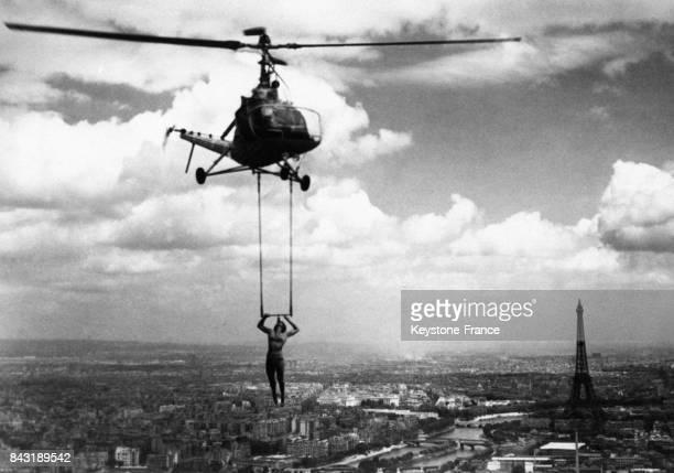 Andrée Jam acrobate suspendue à un hélicoptère fait des acrobaties audessus de la capitale en juin 1952 à Paris France