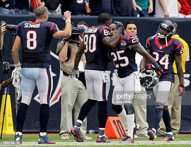 Andre Johnson of the Houston Texans gives Kareem Jackson a hug after Jackson ran an interception back 63 yards for a touchdown against the Tennessee...