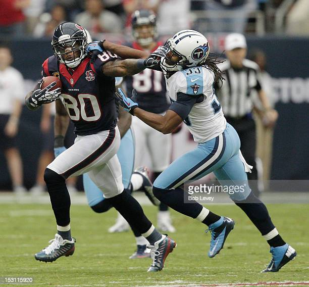 Andre Johnson of the Houston Texans gives Michael Griffin of the Tennessee Titans a stiff arm after making a reception at Reliant Arena at Reliant...